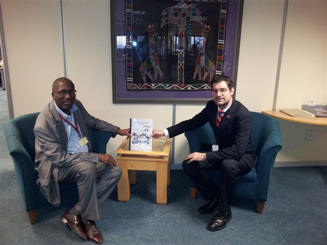 """Prof Geo Quinot (right) presents the research report titled """"An Institutional Legal Structure for Regulating Public Procurement in South Africa"""" to Mr Henry Malinga, Chief Director: Policy and Strategy in the OCPO."""